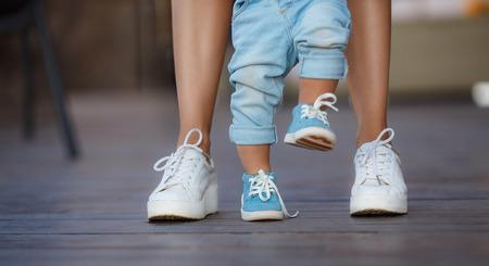 44560554 - the first steps of the kid, mom in white sneakers with a young son, dressed in blue pants and blue shoes, a warm summer day and learn to walk in the street, the first steps, the mother maintains her son.